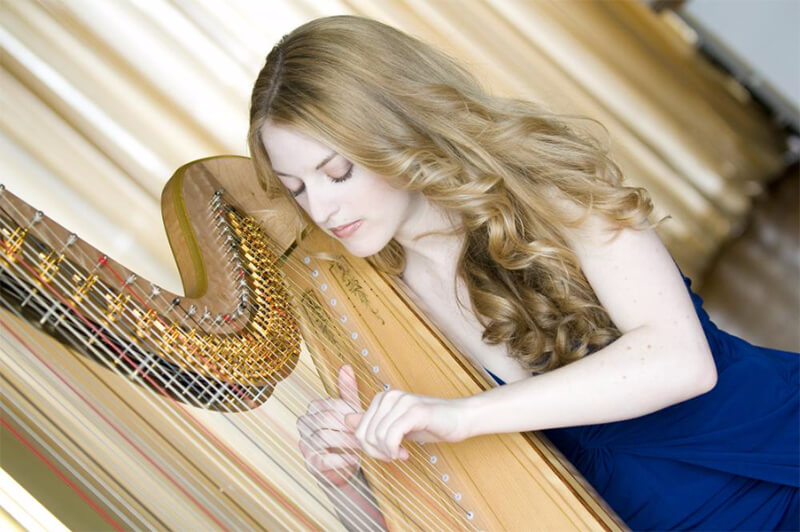 Photo of Dr. Michelle Gott playing a harp