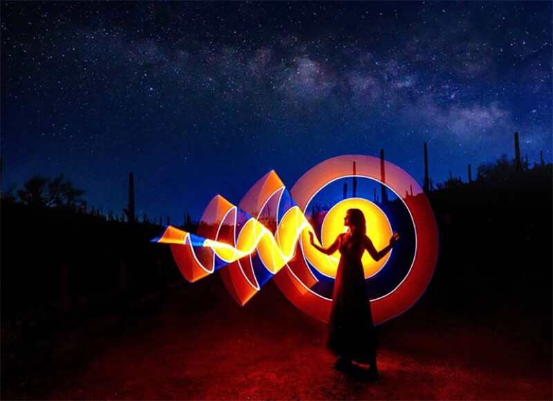 Photo of Kay He with light painting by Daniel Linder and Milky Way as backdrop